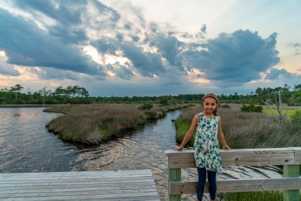 Beautiful clouds in NC behind a child on a pier at sunset.